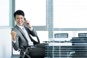 Young businessman on the phone celebratingの写真素材 [FYI02214321]