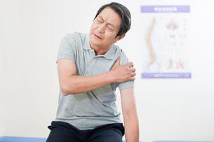 Senior patient rubbing his painful shoulderの写真素材 [FYI02214336]