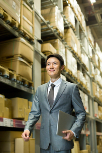 Happy businessman on the move in warehouseの写真素材 [FYI02214362]
