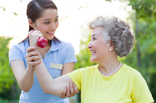 Senior woman exercising with dumbbell in nursing homeの写真素材 [FYI02214369]