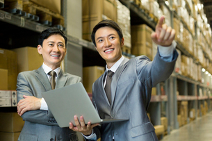 Business partners with laptop in logistic warehouseの写真素材 [FYI02214376]