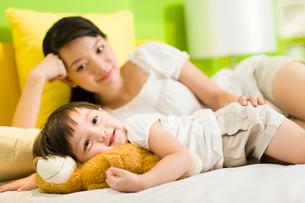 Mother and daughter relaxing in bedroomの写真素材 [FYI02214402]