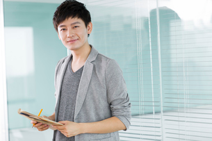 Portrait of young man in officeの写真素材 [FYI02214416]