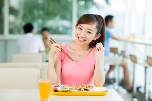 Young woman having a meal in restaurantの写真素材 [FYI02214430]