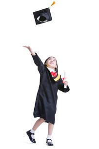 Cute girl in graduation gown throwing mortar boardの写真素材 [FYI02214436]
