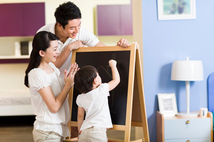 Young family practicing drawing on blackboardの写真素材 [FYI02214491]