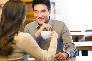 Young couple chatting in cafeの写真素材 [FYI02214496]