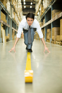 Confident businessman ready to run in warehouseの写真素材 [FYI02214521]