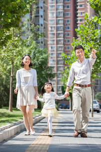 Young parents with daughter strolling on sidewalk hand in handの写真素材 [FYI02214537]