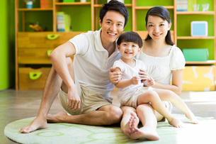 Portrait of young family sitting on floorの写真素材 [FYI02214548]