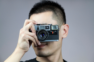 Young man taking photos with old-fashioned cameraの写真素材 [FYI02214553]