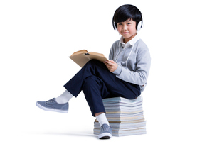 Cute boy with headphone readingの写真素材 [FYI02214590]