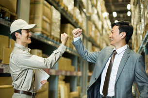 Young logistics staff punching the air with businessmanの写真素材 [FYI02214619]