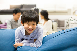Cheerful boy in furniture shop with parentsの写真素材 [FYI02214622]