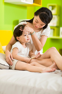 Mother putting her hand on sick daughter's foreheadの写真素材 [FYI02214626]