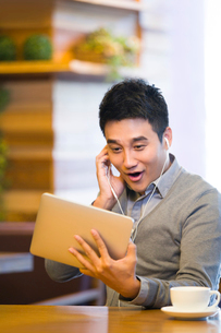 Young man enjoying videos in digital tablet in coffee shopの写真素材 [FYI02214631]