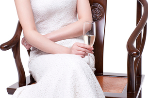 Woman sitting in chair with champagne fluteの写真素材 [FYI02214692]