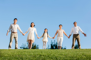 Big family holding hands in a row in a parkの写真素材 [FYI02214700]