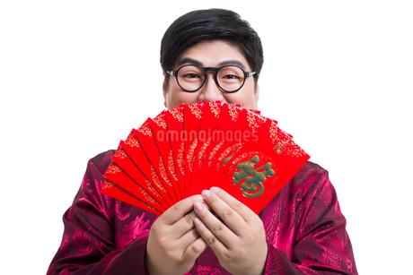 Chubby young man with red packets celebrating Chinese New Yearの写真素材 [FYI02214709]