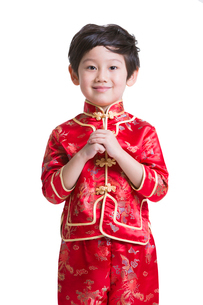 Cute boy in traditional clothing greeting for Chinese New Yearの写真素材 [FYI02214725]