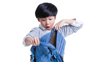 Cute schoolboy opening book bag with surpriseの写真素材 [FYI02214753]