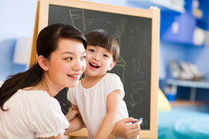 Mother and daughter drawing on blackboardの写真素材 [FYI02214756]