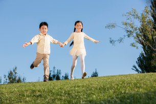 Cute little girl and boy to be flying in a parkの写真素材 [FYI02214775]