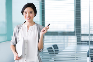 Young businesswoman with laptop in the officeの写真素材 [FYI02214808]