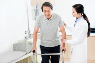 Doctor helping patient with walkerの写真素材 [FYI02214812]