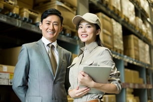 Female logistics staff with businessman in warehouseの写真素材 [FYI02214829]