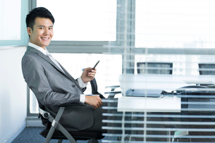 Portrait of businessman with mobile phone in officeの写真素材 [FYI02214898]