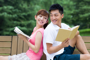 Young couple reading books in parkの写真素材 [FYI02214953]