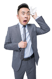 Young businessman wiping sweat with terrified expressionの写真素材 [FYI02214960]