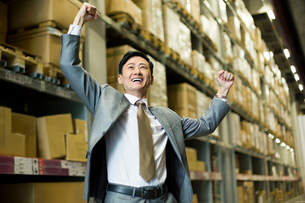 Cheerful businessman punching the air in warehouseの写真素材 [FYI02214982]