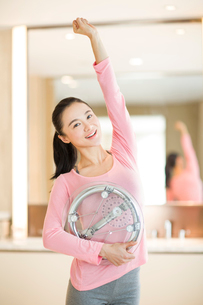 Happy young woman holding weight scaleの写真素材 [FYI02215012]