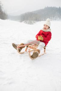 Happy girl sliding on a sledの写真素材 [FYI02215018]