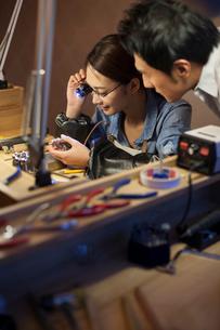 Female jeweler examining jewelry with loupeの写真素材 [FYI02215155]
