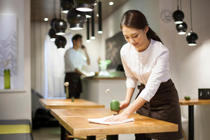 Young waitress wiping tableの写真素材 [FYI02215188]
