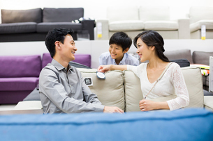 Happy family shopping for sofa in furniture shopの写真素材 [FYI02215191]