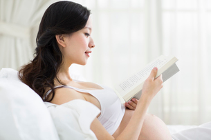 Pregnant woman reading in bedの写真素材 [FYI02215192]