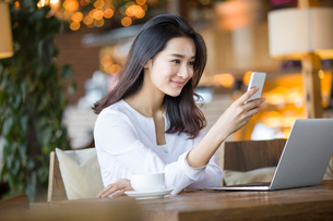 Young woman using smart phone in cafeの写真素材 [FYI02215216]