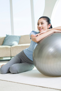 Happy young woman leaning on fitness ballの写真素材 [FYI02215226]