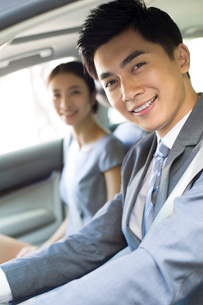 Young businessman driving car with his wife sitting next to himの写真素材 [FYI02215228]