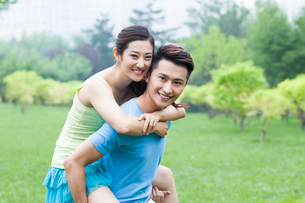 Young man giving her girlfriend a piggy back rideの写真素材 [FYI02215238]