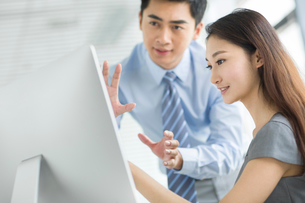 Young businesswoman and businessman talking in officeの写真素材 [FYI02215250]