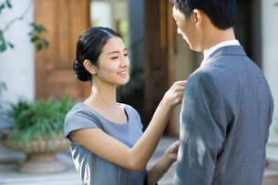 Young woman adjusting her husband's tieの写真素材 [FYI02215282]
