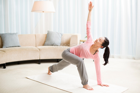 Young woman practicing yoga in living roomの写真素材 [FYI02215320]