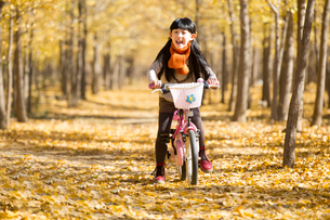 Little girl cycling in autumn woodsの写真素材 [FYI02215373]