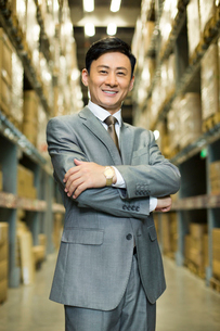 Confident businessman arms crossed in logistic warehouseの写真素材 [FYI02215392]