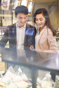 Young couple choosing cakes in bakeryの写真素材 [FYI02215410]